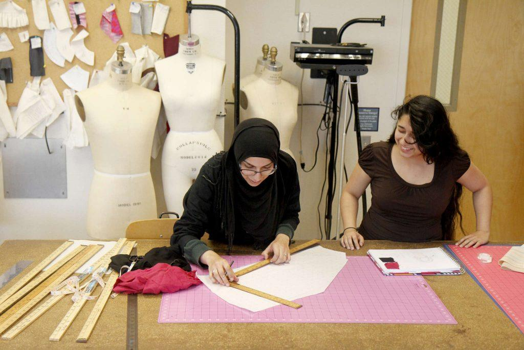 Sara White, (left) and Ruth Reyes laugh while they design a bag for Ruraq Maki, a non-profit that creates economic opportunities for low income women Tuesday, Feb. 17. (Angelica Ekeke / Xpress)