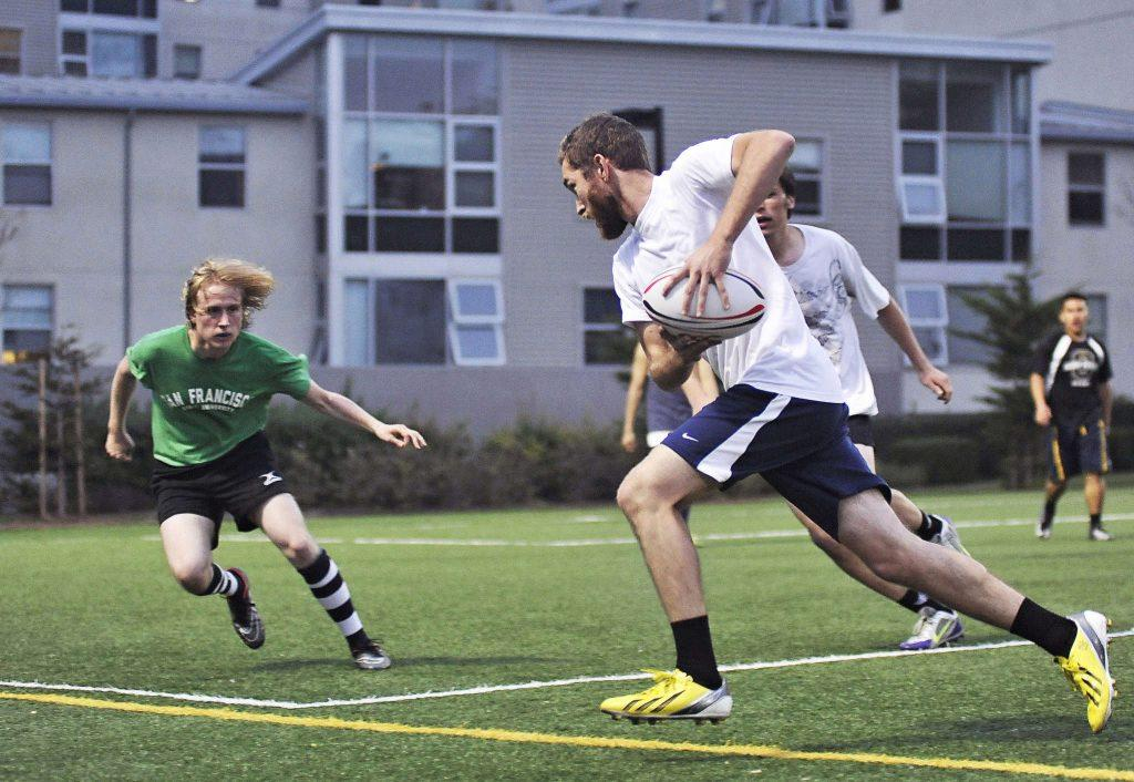 Nathan Wroth prepares to tackle Justin Dawdy as he sprints the ball toward the end zone during a scrimmage at SF State rugby practice on the West Campus Green on Monday, Feb. 16, 2015.