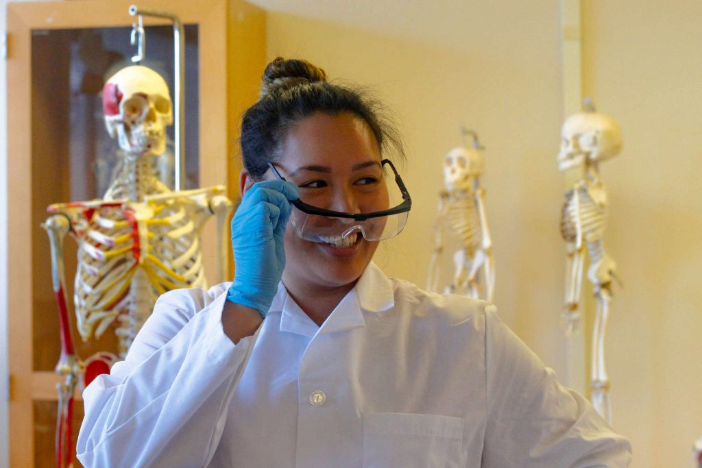 SF State senior Rachel Morales puts on her glasses in the dry lab as she prepares to dissect cadavers for her human anatomy class Thursday, March 5. 2015. (Angelica Ekeke / Xpress)