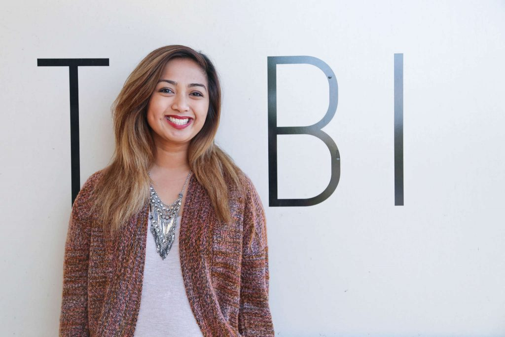 SF State alumna Mayette Santos, community coordinator of the clothing website TOBI, takes a moment of her work day at the office in South San Francisco Monday, March 2. (Zhenya Sokolova / Xpress)