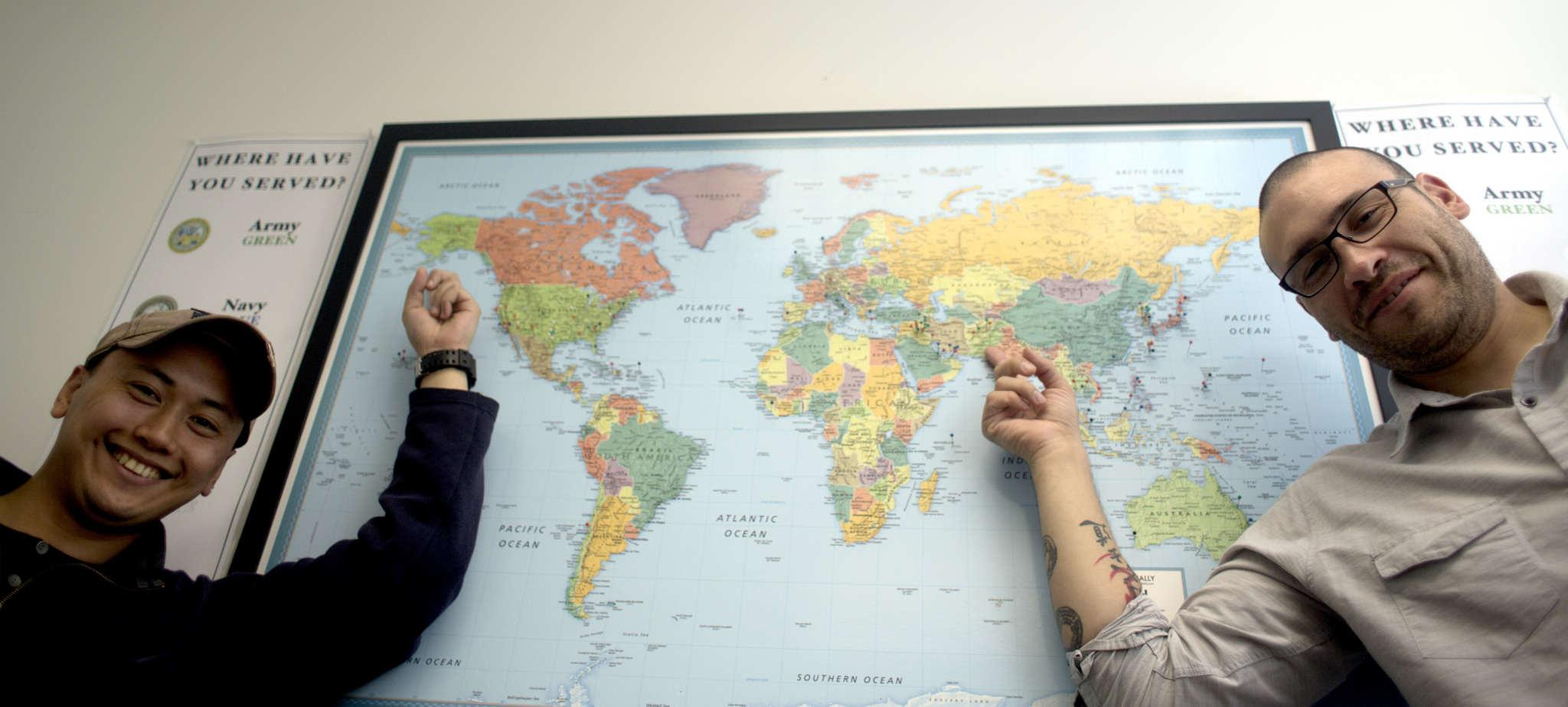 JP Sacramento, right, electrical engineering major and Veteran formally stationed in Alaska and Anthony Rueda, graduate student and Veteran formally stationed in Fort Bliss, Texas point to their stations locations on a map in the  Veterans Services Center at SF State Monday March 2. (Emma Chiang / Xpress)