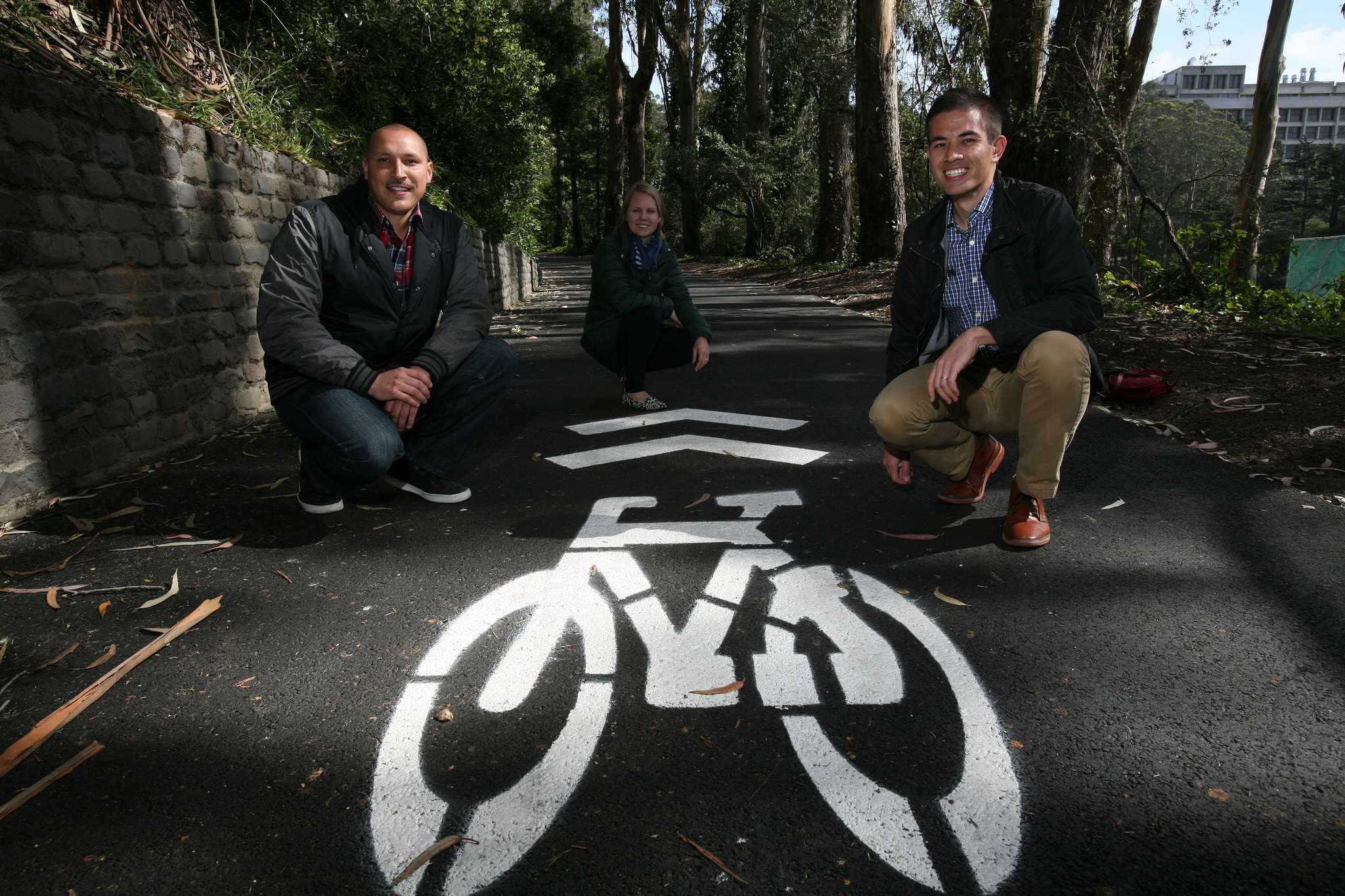 (From right) Nick Kordesch, Caitlin Steele, both are the Sustainability Coordinators at SF State, and Miguel Guerrero, the student coordinator, kneels down next to the newly painted bike path sign which runs along the east side of Cox stadium Monday, March 2. (Daniel Porter / Xpress)