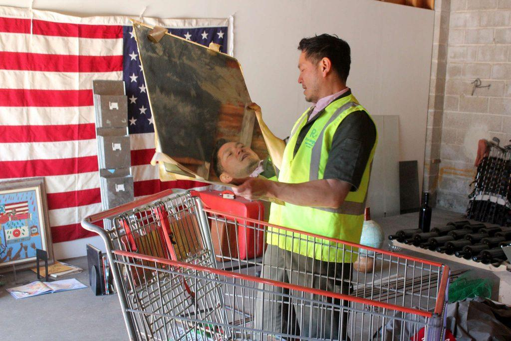 Michael Arcega collects thrown away materials into a shopping cart to be used to create art in his studio at Recology SF Saturday, Feb. 21, 2015. (Drake Newkirk / Xpress)