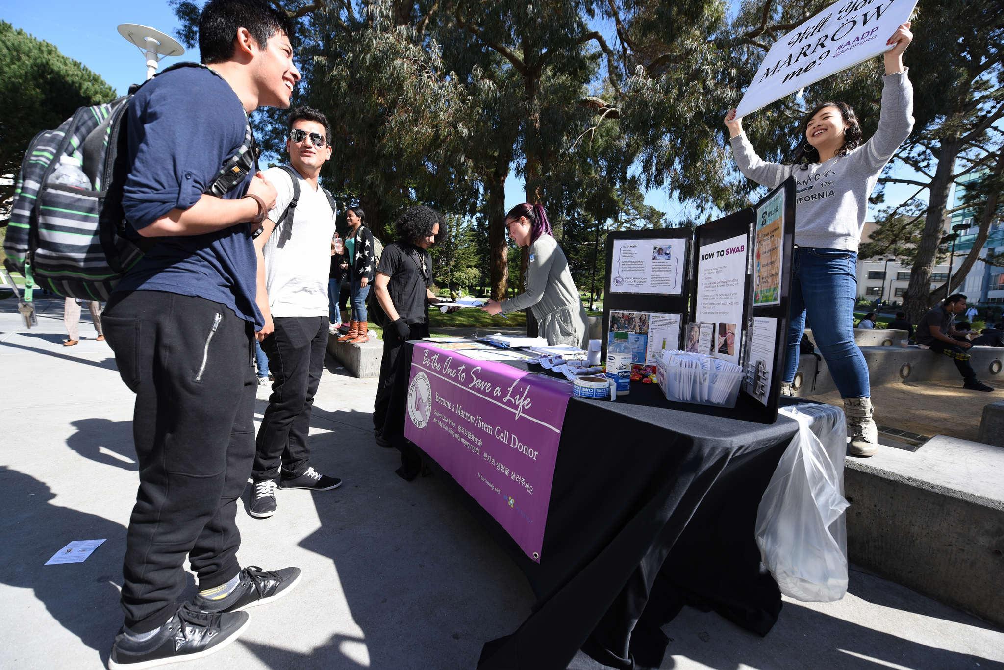 Mauricio Moreno, a junior, smiles at a sign held by Megan Chen saying