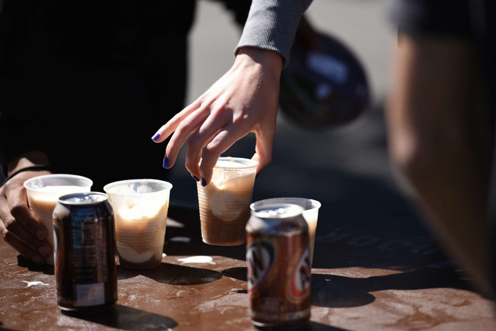 A student grabs a free root beer float at the Founders Day root beer float table at Malcolm X Plaza Wednesday, March 18. (David Henry / Xpress)
