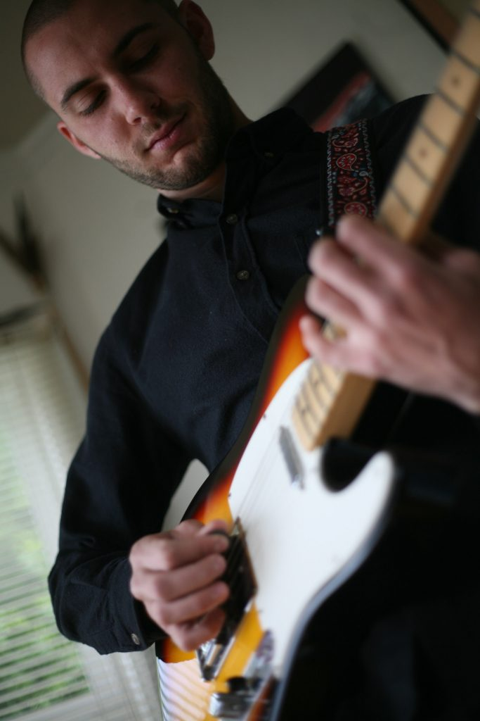 Cory Teese practices music in his room in the Sunset district as he prepares for an up coming show were he will play his complete album from his one-man band Flowers in the Fence Monday, March 30. (Daniel Porter / Xpress)