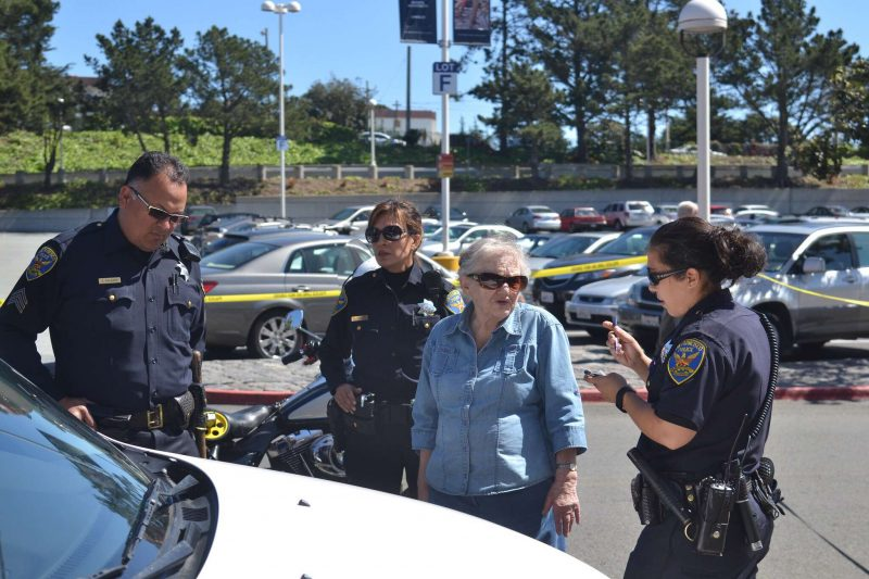 Police interview an elderly woman who struck a mother and daughter in front of The City Sports Club at the Stonestown Galleria Wednesday, March 18. (Helen Tinna / Xpress)
