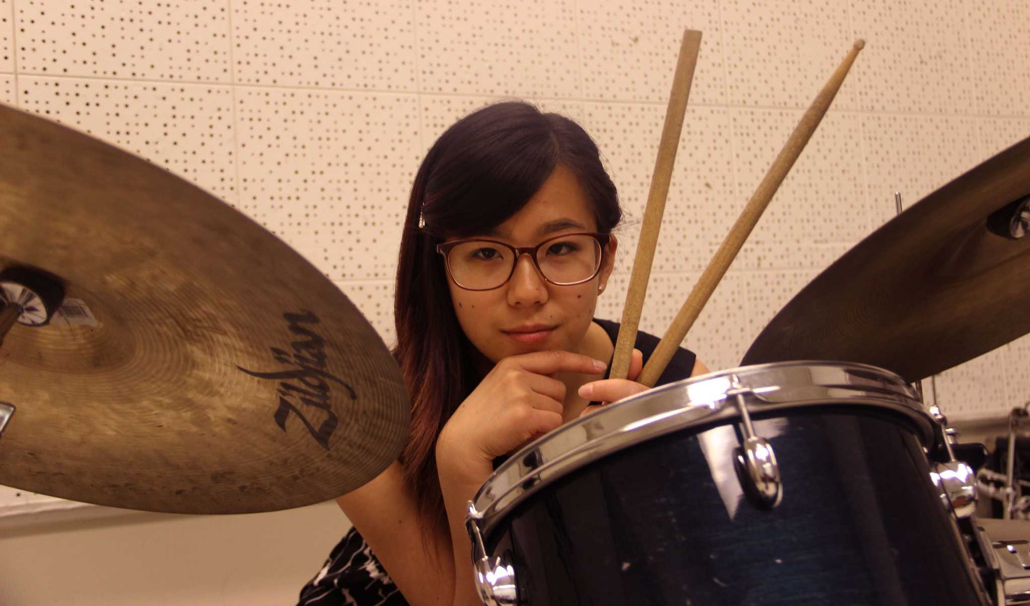 Jazz drummer Lilian Wu sits with her drums in the Creative Art building for a portrait Thursday, April 16. (Angelica Williams / Xpress)