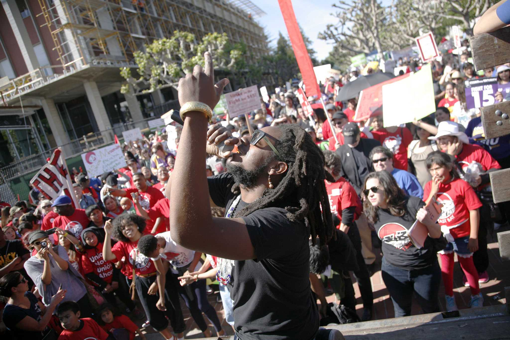 Najee Amaranth, of the The Oakland Mind, performs before hundreds of demonstrators rallying for a $15 minimum wage Wed. April 15, 2015. (Martin Bustamante / Xpress)