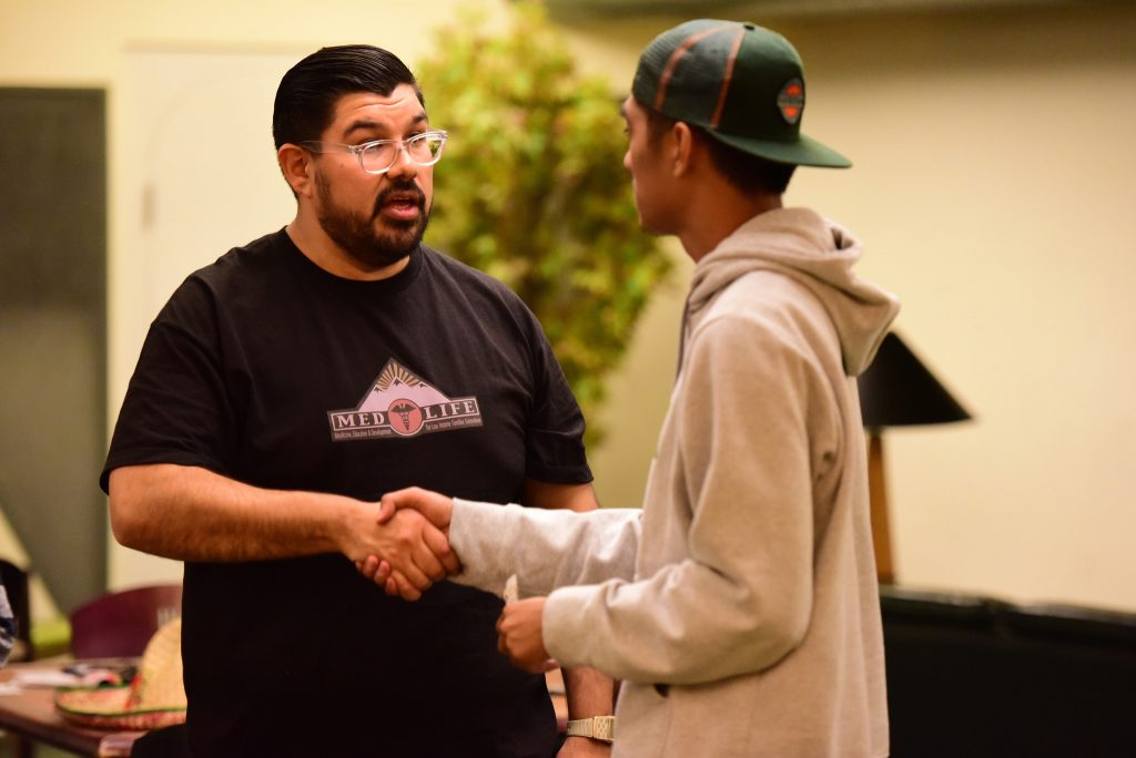 President of SFSU's MedLIfe chapter Adolfo Luna greets a guest at the fundraiser event inside of Menchu Hall Thursday, April 2. (David Henry / Xpress)