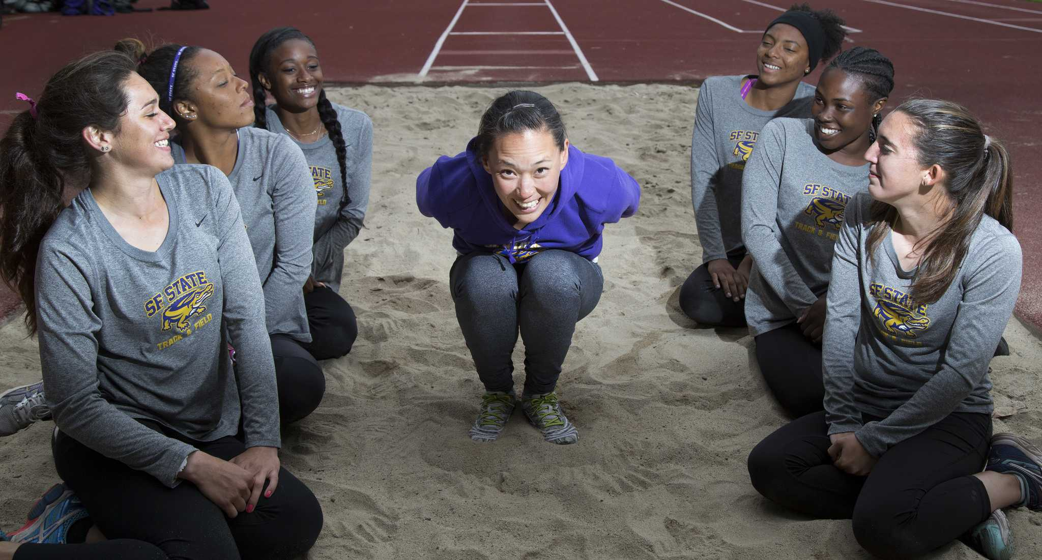 Marissa Chew, assistant coach for the women's long and triple jump athletes, jumps into the sand with her team beside her at Cox Stadium Tuesday, April 21.