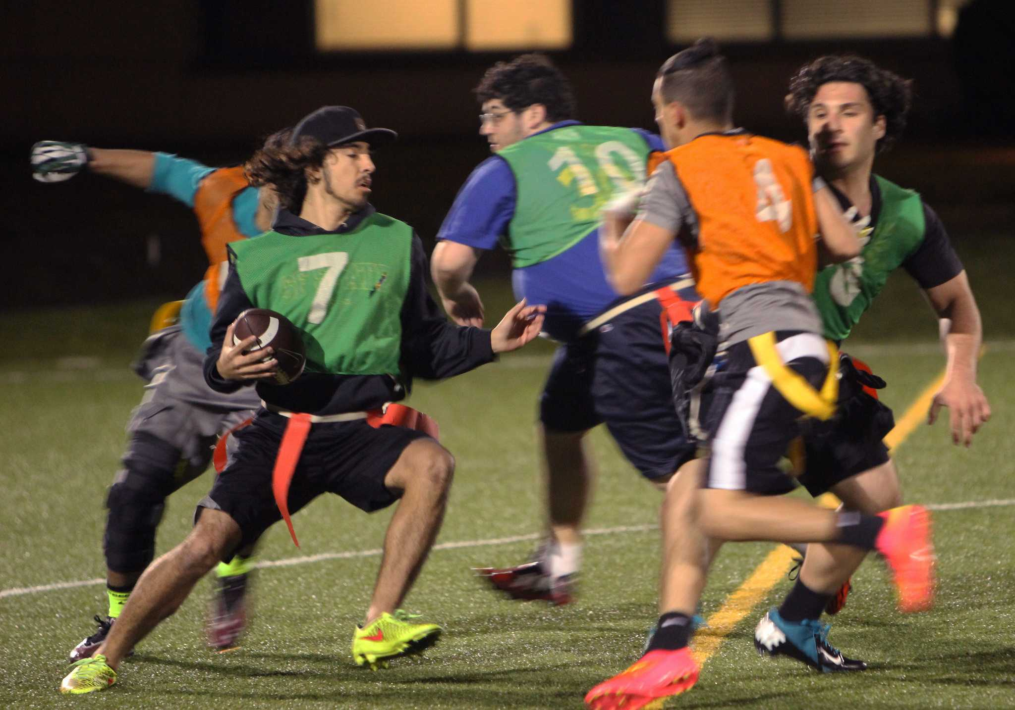 Koby Barela # 7 runs with the ball as a few players block a path for him during SF State's intramural flag football game Monday, April 6. (Angelica Williams / Xpress)