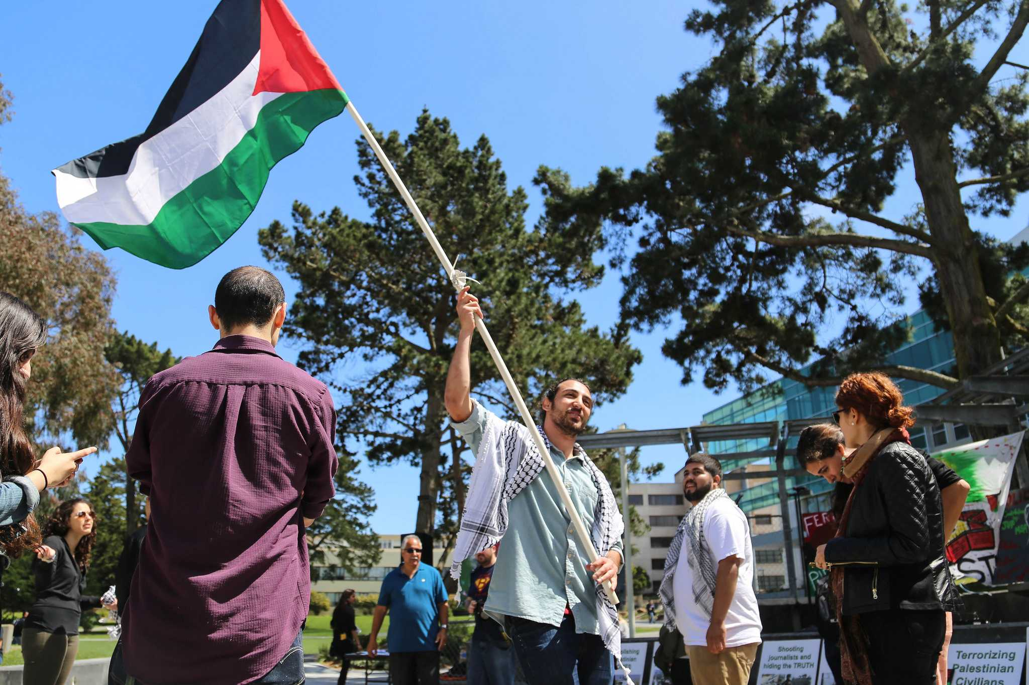 A General Union of Palestine Students, GUPS, member Awwad Yasin waives the Palestinian flag during the Israeli Apartheid Week Rally in Malcolm X Plaza Friday, April 17. (Zhenya Sokolova / Xpress)