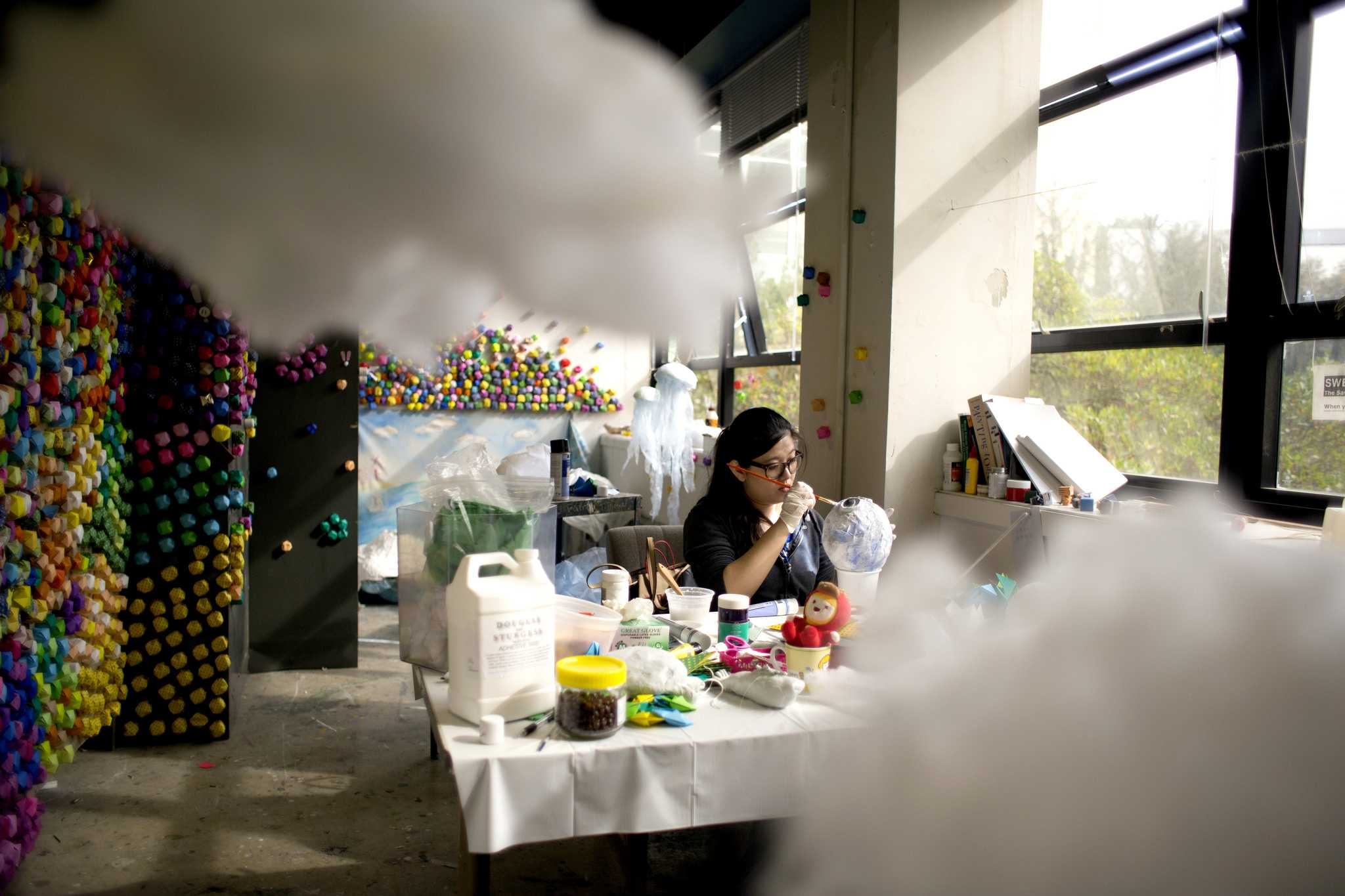 Shan Jiang fine arts graduate student paints a toy fish in her studio on Tuesday March 10, part of her recent project of sea world creatures. (Emma Chiang/ Xpress)