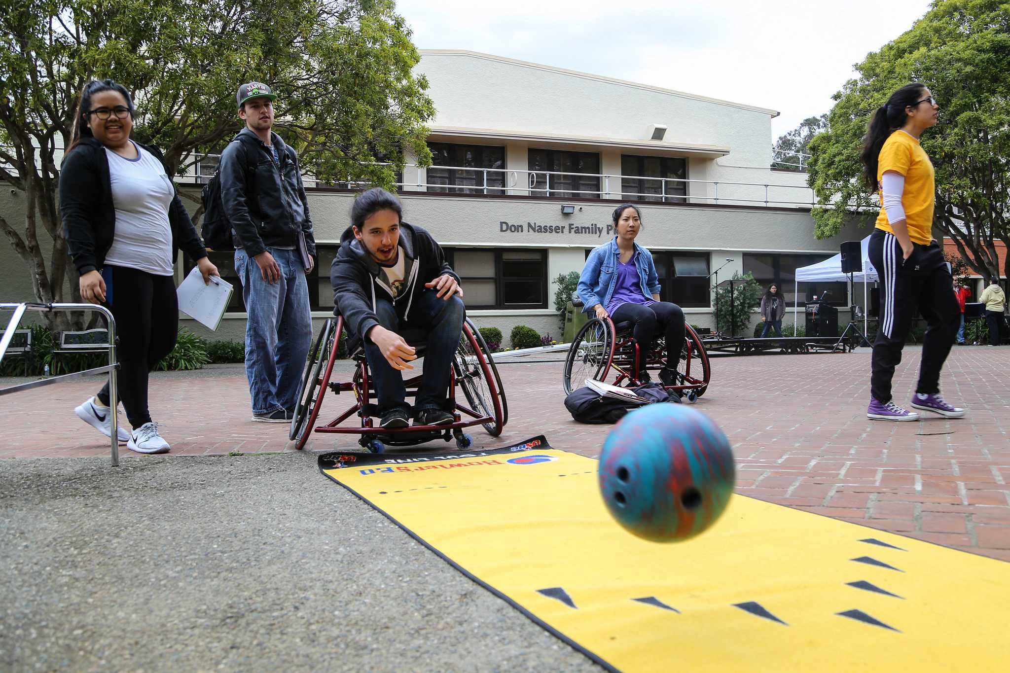 A parks and recreation major Russell Meglio tries bowling from a wheelchair at Accessible Adventures Day in front of the gym in Don Nasser Family Plaza Thursday, May 7. (Kate Fraser / Xpress)