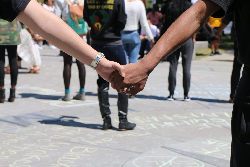 Students and members of the Black Student Union hold hands at the Malcolm X celebration at Malcolm X Plaza on Thursday April 30. (Marlene Sanchez / Xpress