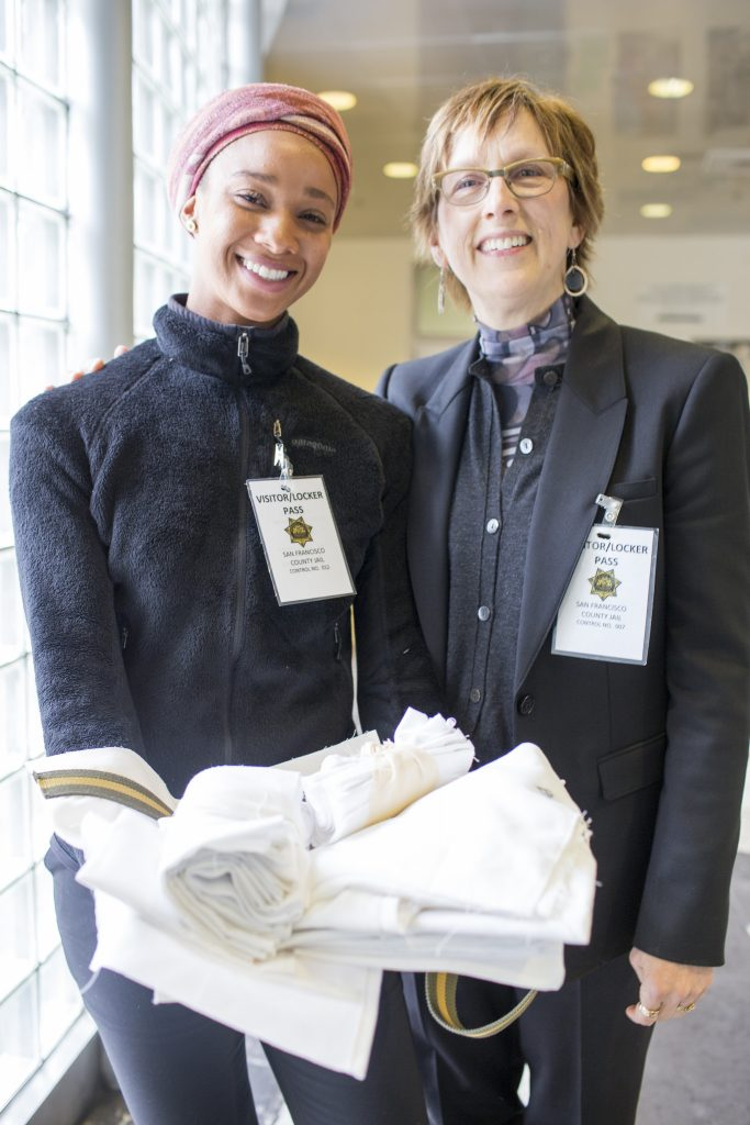 Dr. Connie Ulasewicz and Keno Greene, one of the five graduate students in a Social Entrepreneurship class, present fabric to student inmates who will use to make tote bags at the San Francisco County Jail Mon. May 4, 2015. (Martin Bustamante / Xpress)
