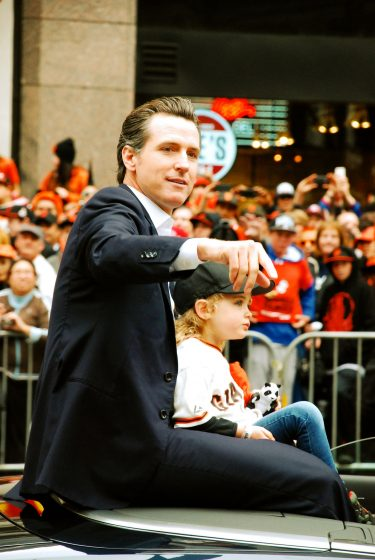 Former San Francisco mayor Gavin Newsom hold his daughter Montana while waving at Giants' fans during the 2012 San Francisco Giants World Series parade Wednesday, Oct. 31 2012. (Katie Lewellyn / Xpress)