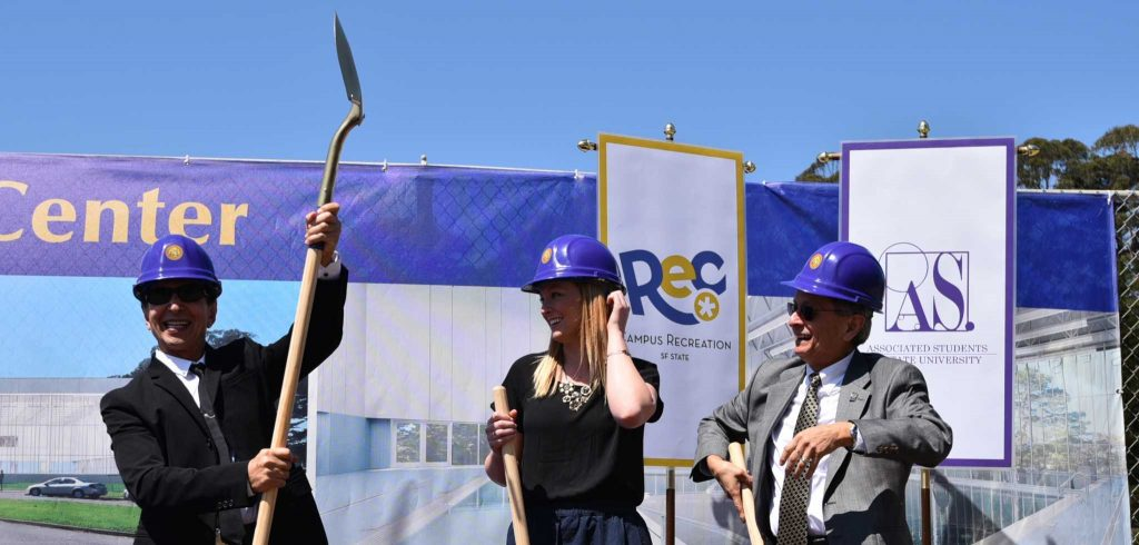 (From left) SF State alumnus and Bebe Stores founder Manny Mashouf,  raises his shovel next to Phoebe Dye, president of Associated Students, Inc. and President Leslie E. Wong during the Mashouf Wellness Center groundbreaking ceremony at the SF State softball field Thursday, June 25, 2015. (Xpress / Qing Huang)
