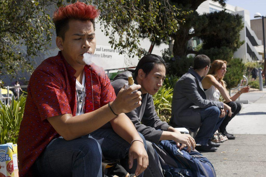 Sober Vun, an undeclared major, (left) uses his vaporizer while Calvin Thai, an information systems major, smokes a cigarette along Holloway Ave. at SF State Monday, Aug. 31. (Ryan McNulty / Xpress)