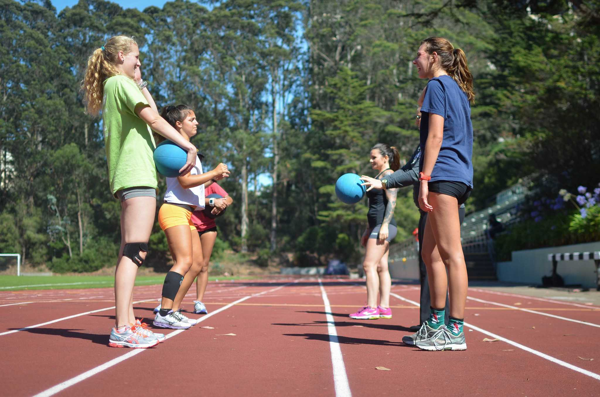Members of the SF State women's cross country team throw  medicine balls to each other during practice at Cox Stadium Monday, August 24. (Melissa Minton / Xpress)