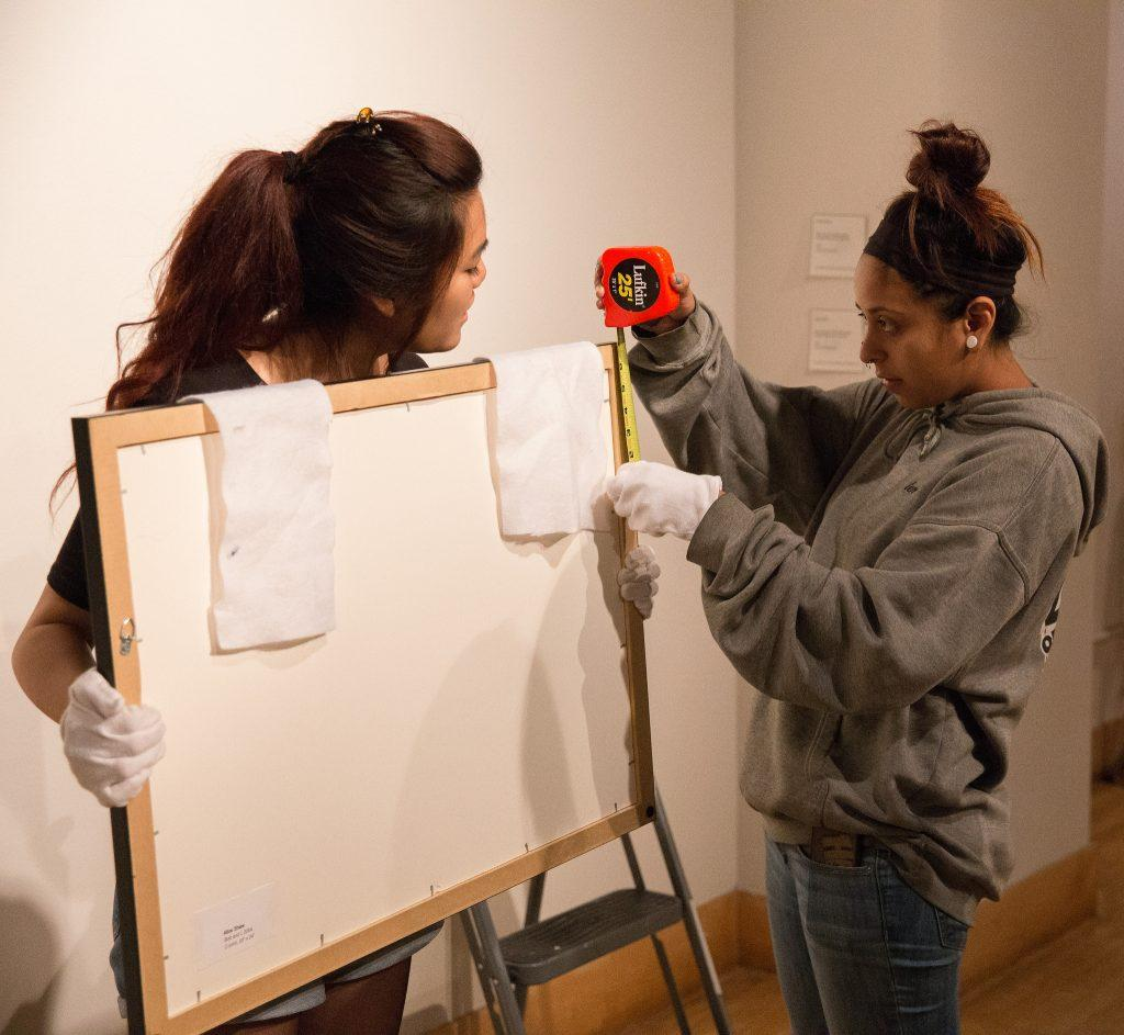 Nanami Gibo (left) and Alyssa Ybarra hang artwork for the PLAY exhibition at SF State's Fine Arts Gallery, Friday, Sept. 11, 2015.  The exhibition opens Saturday, Sept. 19. (Brian Churchwell / Xpress)