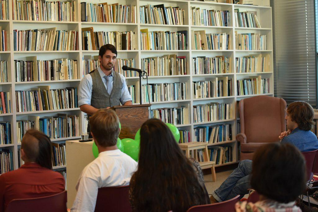 Austin Messick, left, a graduate student of poetry, reads a poem to the audiences during the first poetry reading event of the semester held by Velro (Velvet Revolution Reading Series) at the poetry center at Humanities Building at SF State Monday, Aug. 31. (Xpress/Qing Huang)