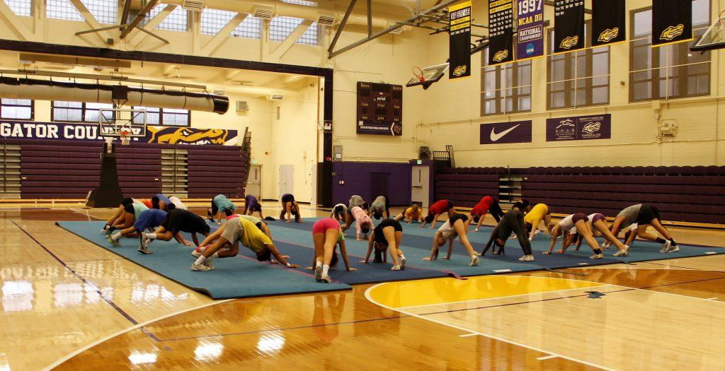 SF State cheerleaders stretch out their legs before practicing in the main gym at SF State Friday Sept. 4, 2015. (Imani Miller/Xpress)