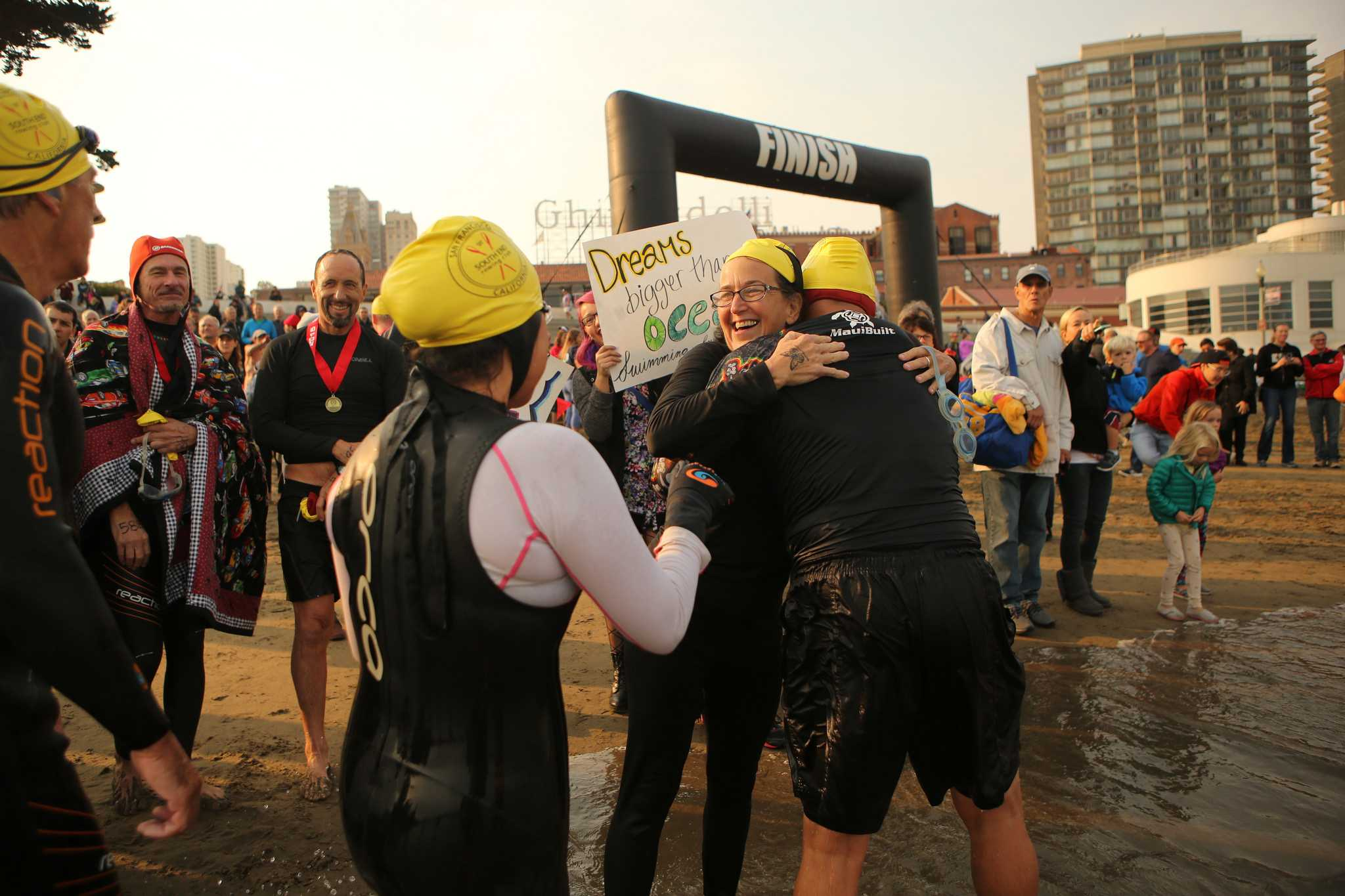 Nancy Jodaitis (left), an AB 540 financial aid counselor at SF State, hugs SF State alumni Marcos Tapia (right) after swimming to shore during the Alcatraz Invitational on Sunday, Sept. 13, 2015 in San Francisco, Calif. (Joel Angel Juárez /  Xpress)