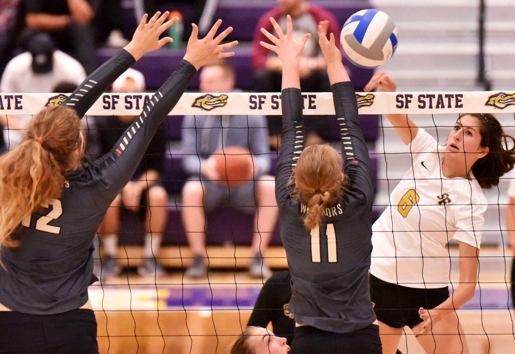 Jaclyn Clark (6), outside hitter for SF State Gators, spikes the ball against Stanislaus State Warriors middle blocker  Taylor Massengale (12), and setter Maddi Seidl (11), during the game at the Swamp in SF State Tuesday, Sept.29. SF Gators lost 1-3. (Qing Huang / Xpress)