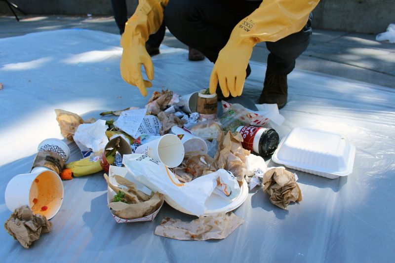 Amir Sahit sorts through waste during a waste audit demonstration at the Vendors Sustainability Project Launch in SF State's Malcolm X Plaza Wednesday, Sept. 23. (James Chan / Xpress)