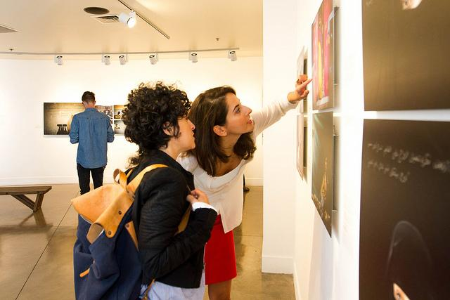 SF State alumnus Shoky Monfared and photographer Golnaz Shahmirzadi discuss an art piece from the