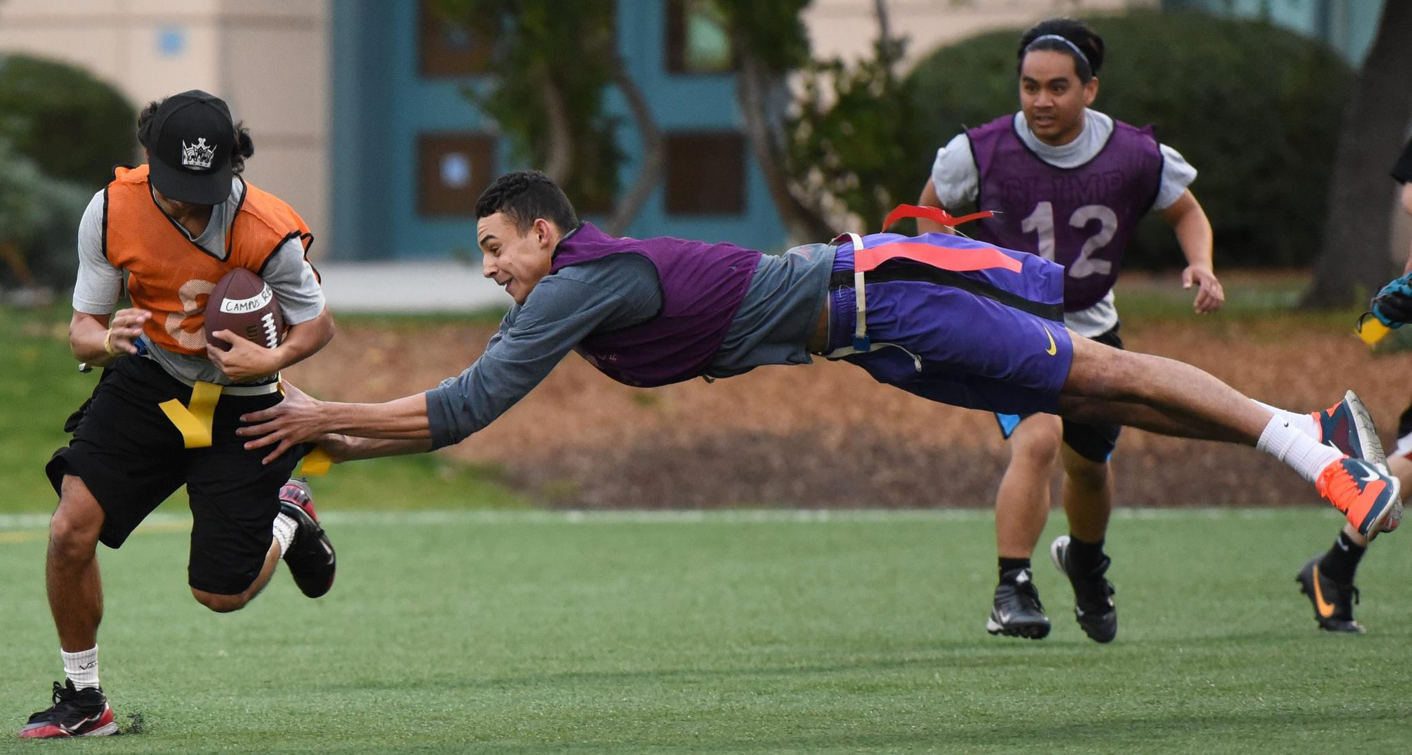 Taurean Oram (7) of the Wolf Pack dives through the air as he grabs a Swolldiers player's flag in an intramural flag football game at the West Campus Green field Monday, Sept. 28. (David Henry / Xpress)