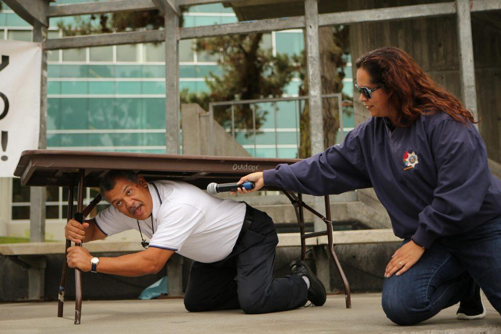 University+Police+Department+%28UPD%29+Sgt.+Abe+Leal+%28left%29+demonstrates+earthquake+preparedness+procedures+as+UPD+Accreditation+Manager+Martha+Villanueva+%28right%29+holds+a+mic+during+the+annual+California+ShakeOut+Earthquake+Drill+in+Malcom+X+Plaza+at+SF+State+on+Thursday+October+15%2C+2015.+%28Photo+by+Joel+Angel+Ju%C3%A1rez+%2F+Xpress%29