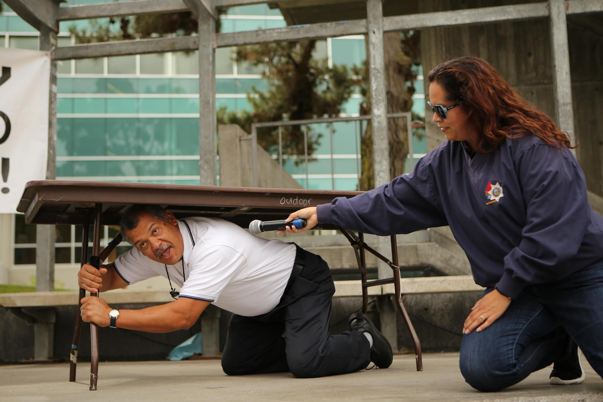 University Police Department (UPD) Sgt. Abe Leal (left) demonstrates earthquake preparedness procedures as UPD Accreditation Manager Martha Villanueva (right) holds a mic during the annual California ShakeOut Earthquake Drill in Malcom X Plaza at SF State on Thursday October 15, 2015. (Photo by Joel Angel Juárez / Xpress)