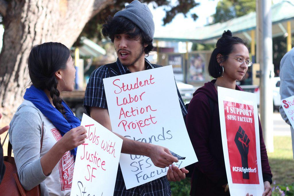 Students Beth Huang (left),  Christian Arriola (middle), and Devin Lee (right), an SF State women and gender studies graduate, hold up their signs during a voting kick off event held by the California Faculty Association on Holloway and 19th Ave. Monday, Oct. 19, 2015. (Alex Kofman / Xpress)