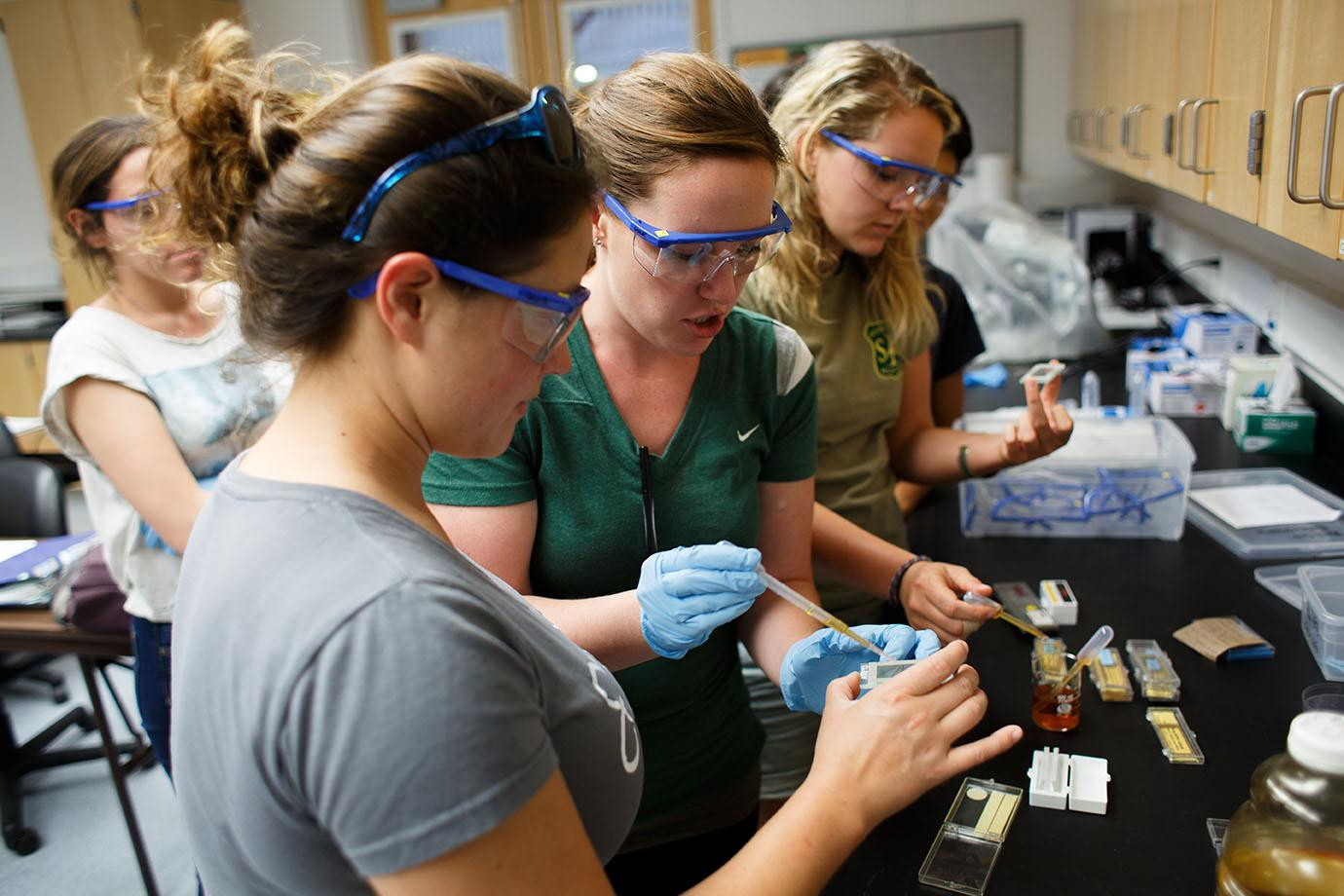 Karen Backe (left) and Lindsay Faye (center), both marine science grad students, prepare a slide with a sample of phytoplankton during their biological oceanography class at The Romberg Tiburon Center on Monday, Sept. 21, 2015. (Ryan McNulty / Xpress)