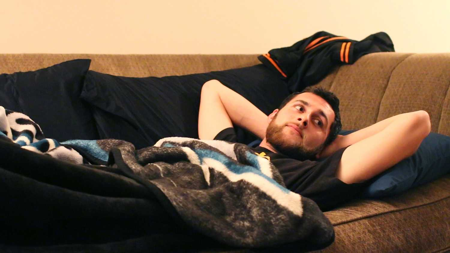 Rudolph Tescallo, senior psychology major, lies on the couch he will be sleeping on for the night at his friend's house at Westlake Village Apartments in Daly City Wednesday, Sept. 23. (Screen Shot Jocelyn Carranza / Xpress)