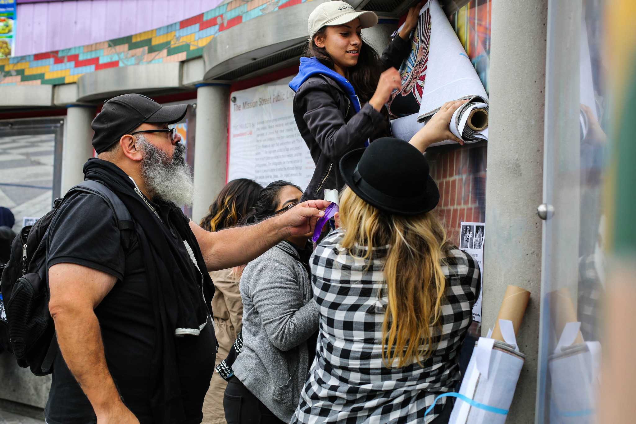 Victor De La Rosa, associate professor at SF State in the Art Department (far left) and his volunteers ( left) Emily Cruz, Veronica Rued ( center) , and Nash Bellows puts up one of his art  pieces at the 16th street Bart station Tuesday, Oct. 27. (Angelica Ekeke/Xpress)