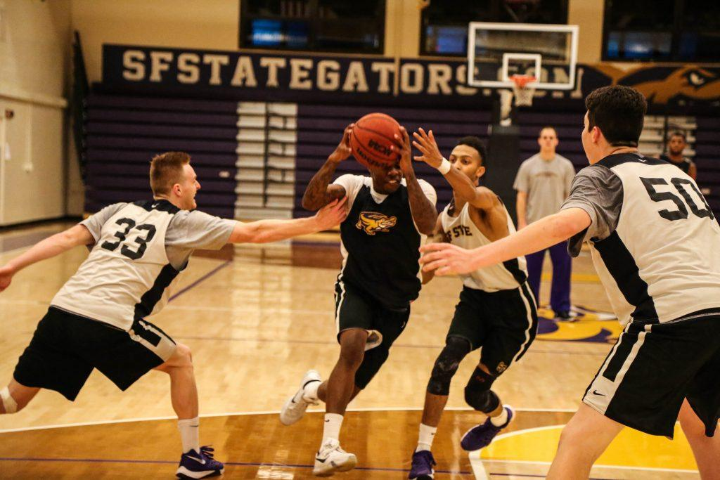 Warren Jackson (1) drives the basketball through the middle of the court while teammates Jon McMurry (33) left, Andre Jones (5) and Ryne Williams (50) guards him during the SF State men's basketball practice Monday, Nov. 2, 2015. (Angelica Ekeke / Xpress)