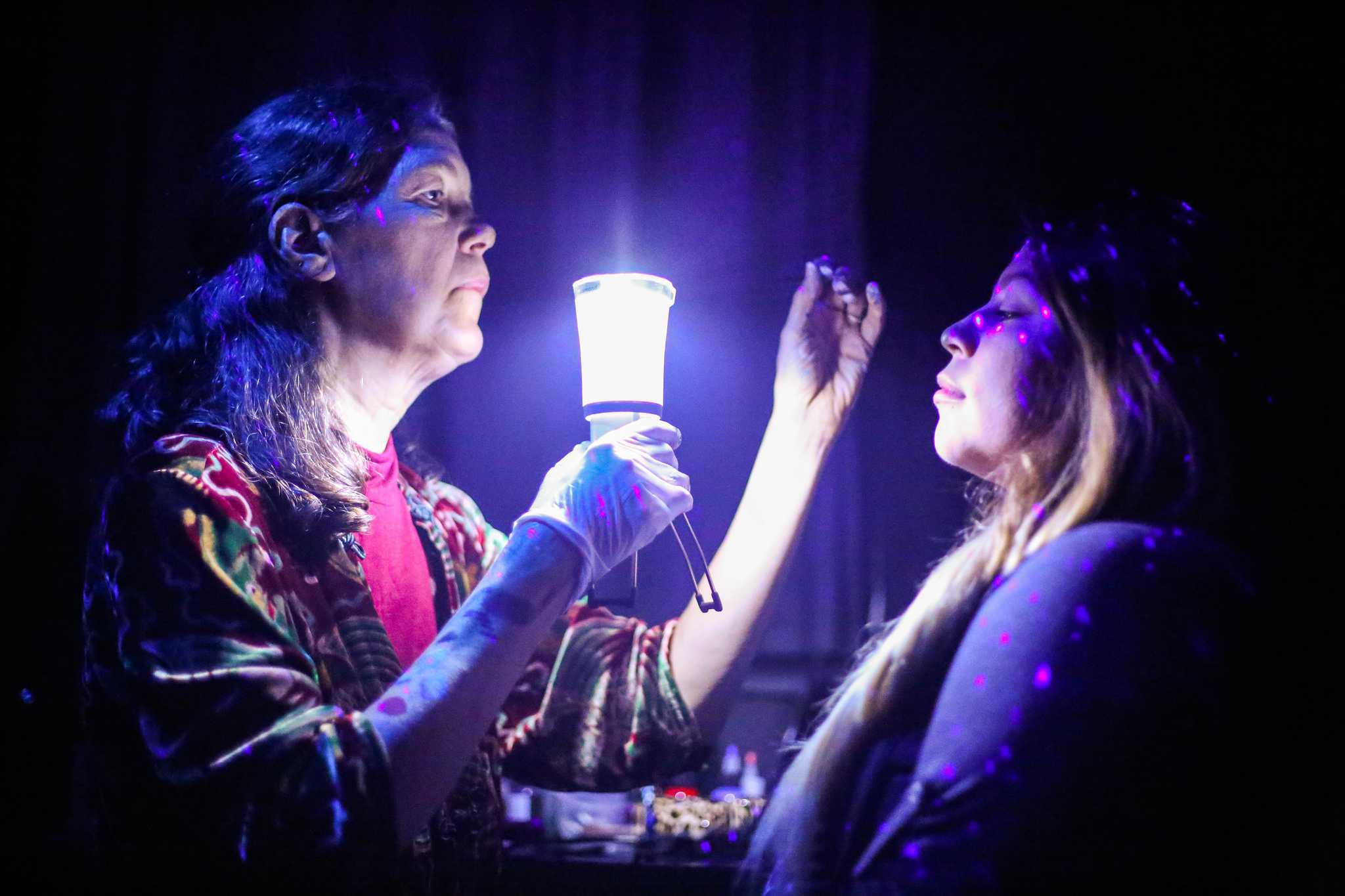Stacey Dennick owner of Auntie Stacey's Face Painting holds a light in front of Carolina Martinez's face durring a face painting session   at the Dia De Los Muertos Fundraising event for All Hands organization at the Raven Bar Wednesday, Nov. 5, 2015. (Angelica Ekeke / Xpress)