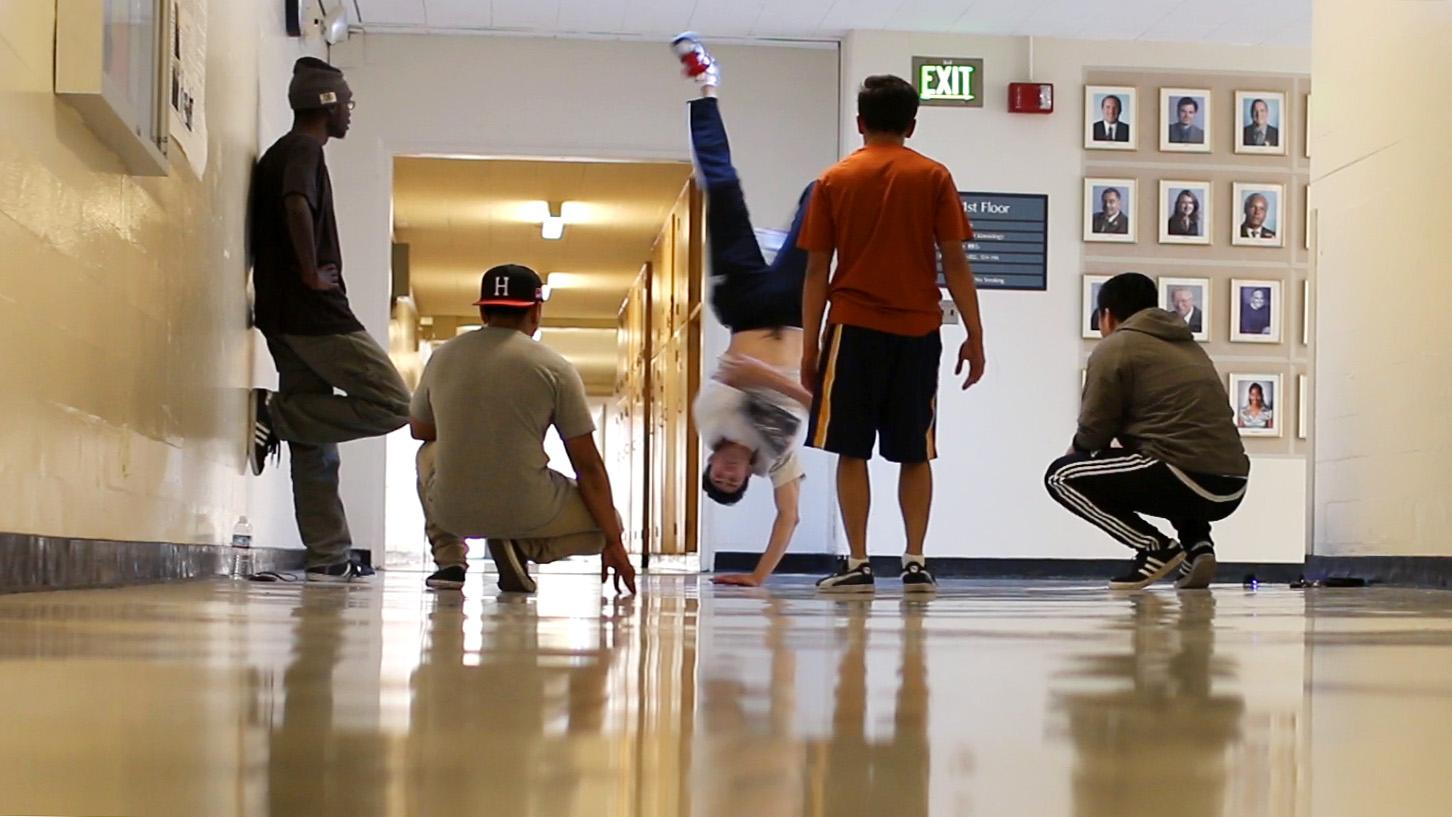 Members of the Hip Hop State of Mind club watch Sean Morales, English major, make a hand stand in the Gymnasium hallway Tuesday, Nov. 3, 2015. (Screenshot by Creo Noveno / Xpress)