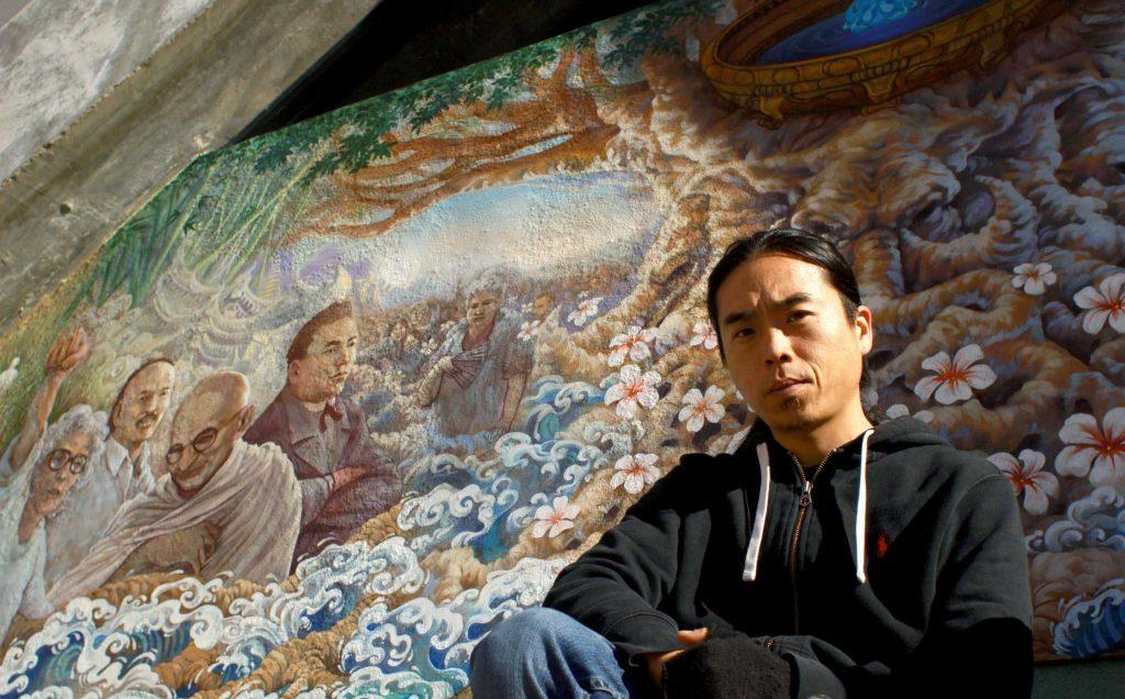 "Muralist David Hyde poses for a portrait in front of of his mural Asian Pacific islanders ""infinite tree of life"" on the side of the Cesar Chavez building at SF State Thursday, Nov. 12, 2015. (Angelica Williams / Xpress)"