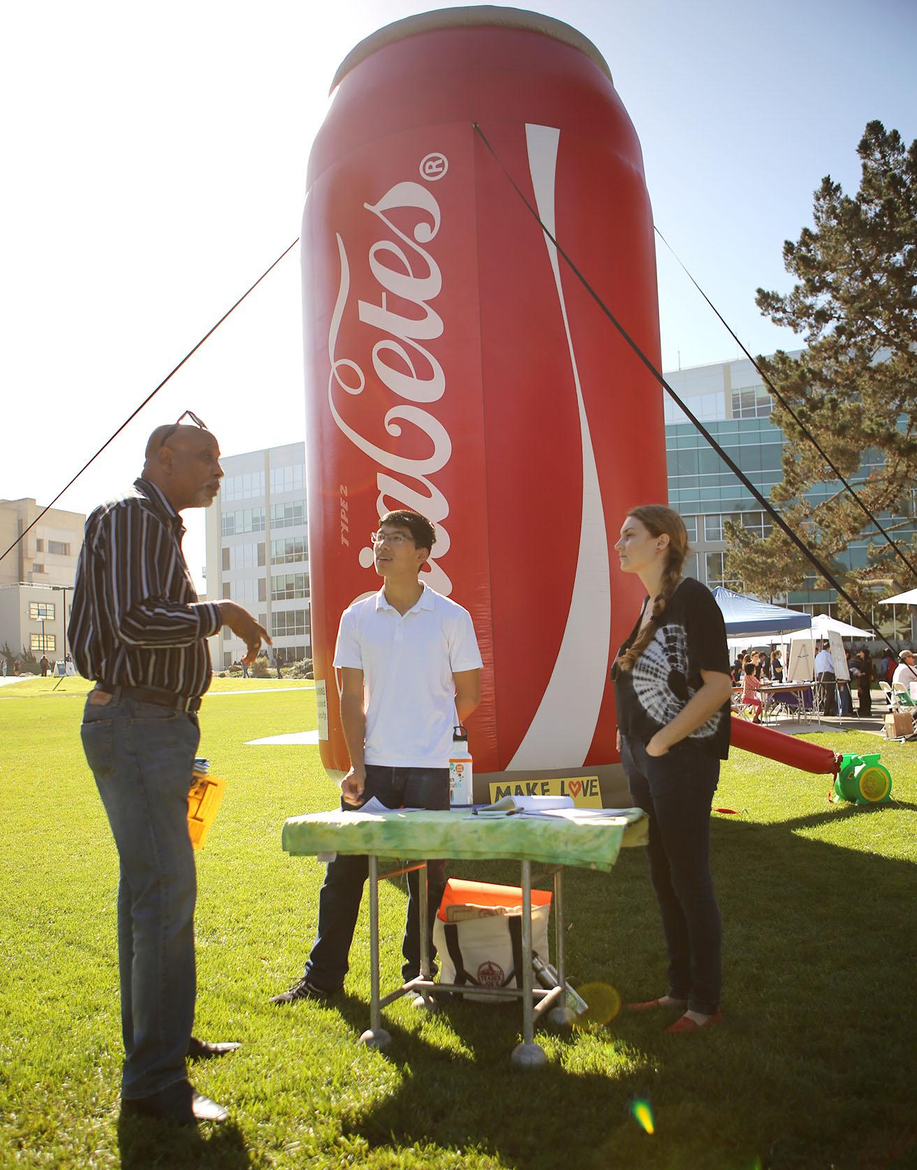 ASI Senior Program Advisor Muata Kenyatta (left) speaks to Real Food Challenge members An Bui (middle), a fourth year geography and history major, and Eden Edell (right), a third year environmental science major, regarding UCorp's proposed exclusive pouring rights partnership with SF State in the quad Wednesday October 21, 2015. (Joel Angel Juárez / Xpress)
