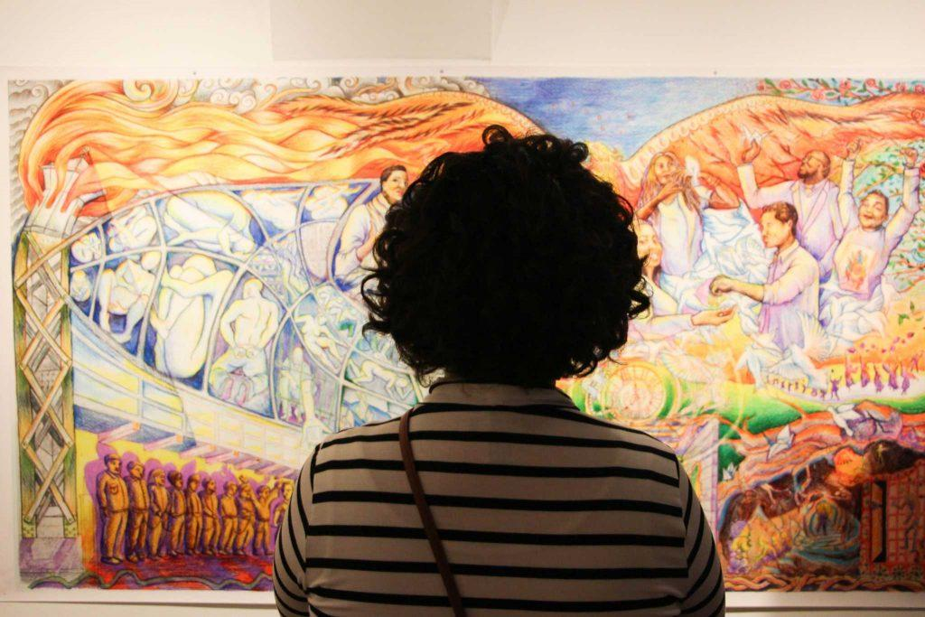 An attendee of the Project Rebound art show in the Cesar Chavez Student Center observes the mural, which is a representation of Project Rebound's focus on