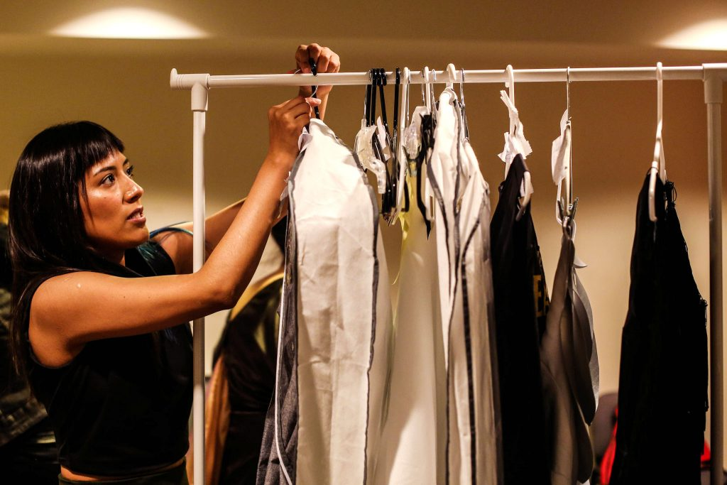 Lia Herrera, SF State fashion design major pulls a garment off of the rack at the Fashion Association Network's fashion show 'Nostalgia' Dec. 4 2015. (Angelica Ekeke/Xpress)