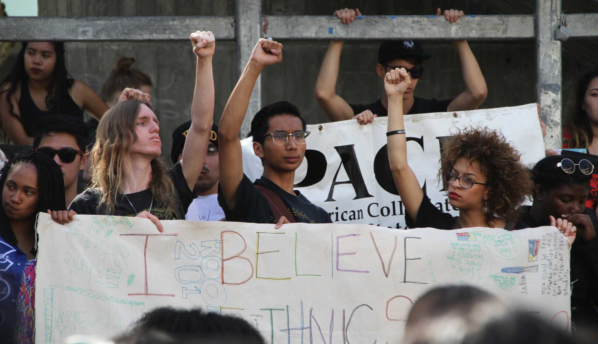 Seanan Kenney, Jon Ray Guevarra, and a fellow student raise their fists and hold a banner saying