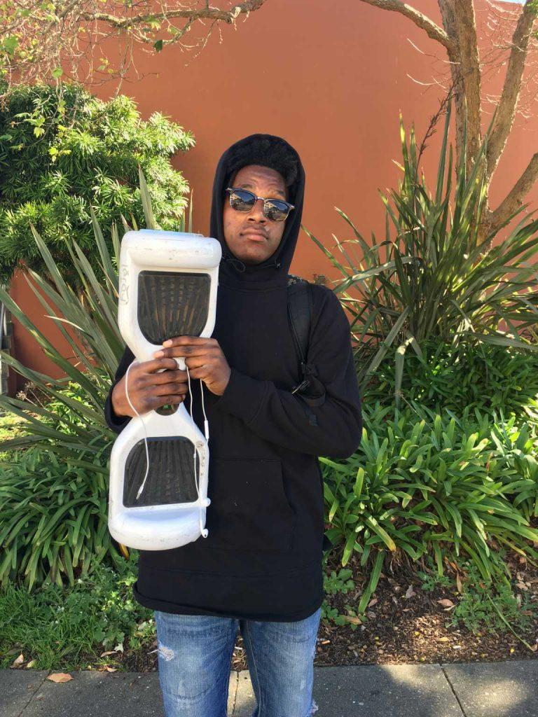Donald Howard, an 18-year-old kinesiology major, poses with his hoverboard at SF State on Monday, Feb. 15.