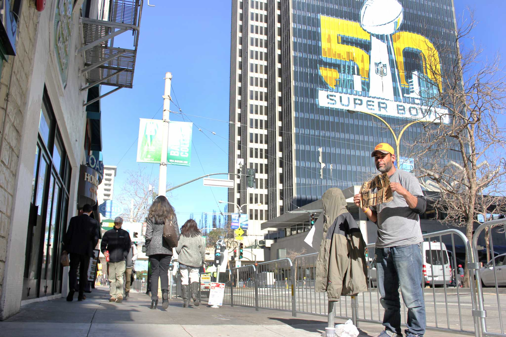 Noble Mitchell (right) holds a sign as people walk by on Drumm Street near the Super Bowl City festivities in San Francisco, Calif., Monday, Feb. 1, 2016. (George Morin / Xpress)