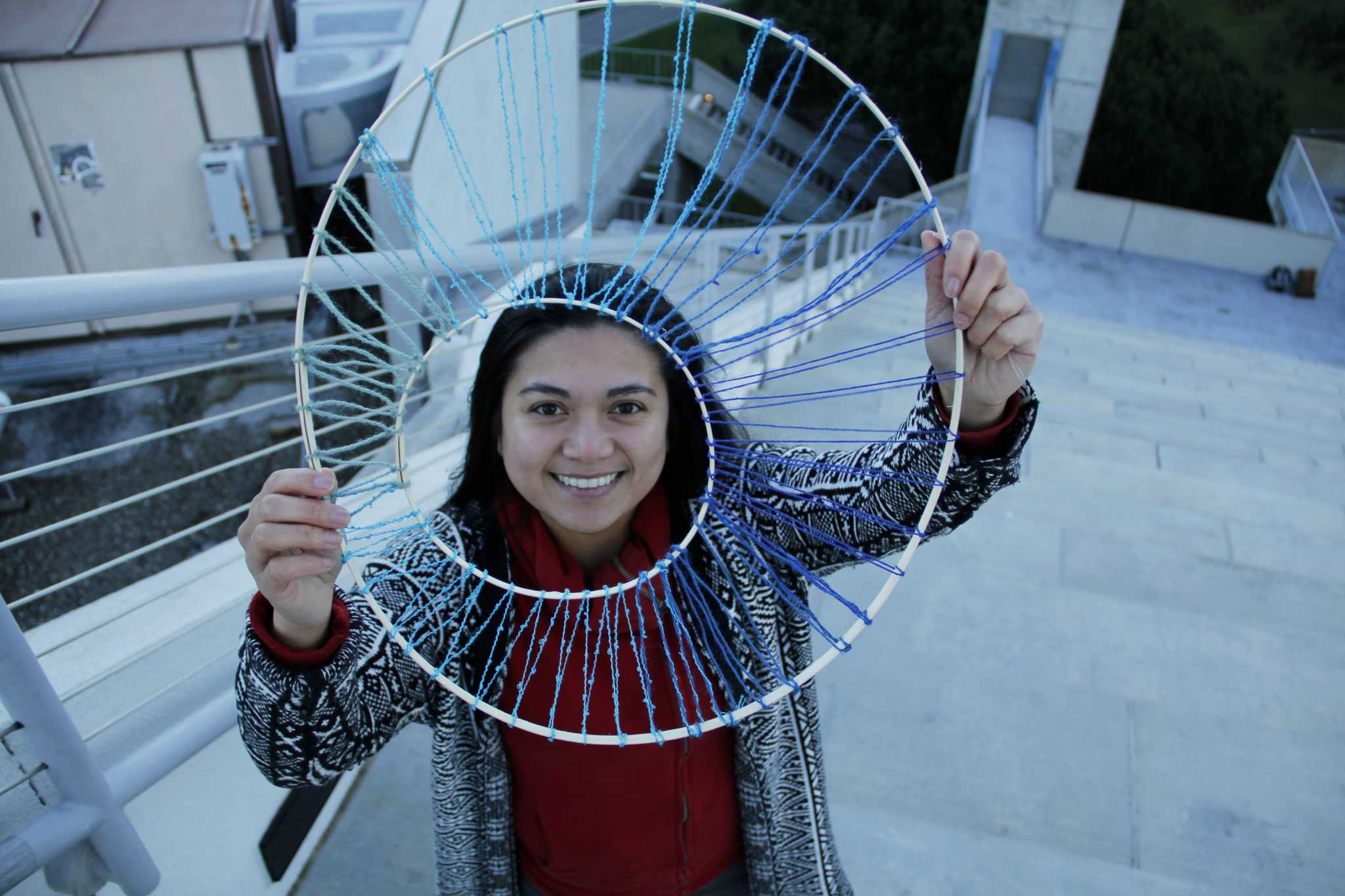 SF State alumna Mona Marcos poses with a piece from the upcoming